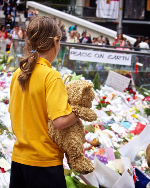 A girl with a teddy bear in Sydney's Martin Place overlooking the flower memorial dedicated to the victims of the Lindt Café siege by a lone gunman, where Tori Johnson and Katrina Dawson were killed on Tuesday 16 December, 2014. (Photo courtesy: JAM Project via Flickr and adapted from original).