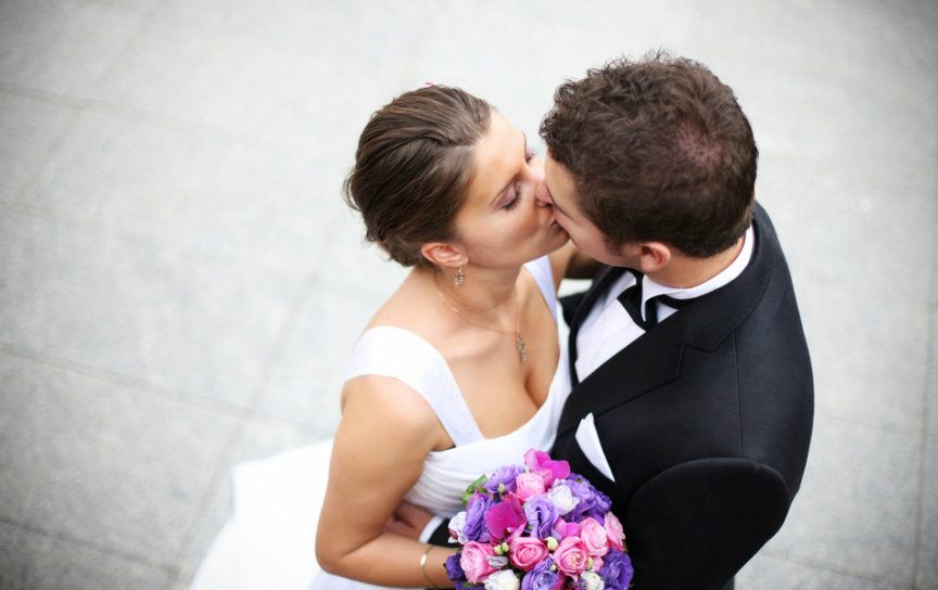 Beautiful picture of a nice young married couple kissing on a street